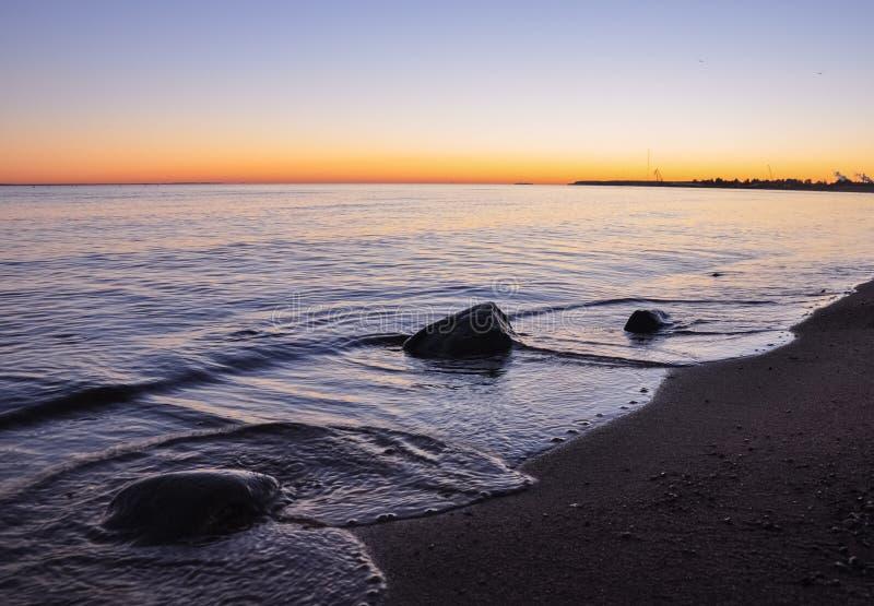 石头在水中,在芬兰湾沙滩的波浪美妙的日落的 库存图片