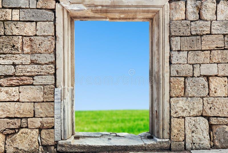 石头墙壁与一个孔的在门下 免版税库存图片