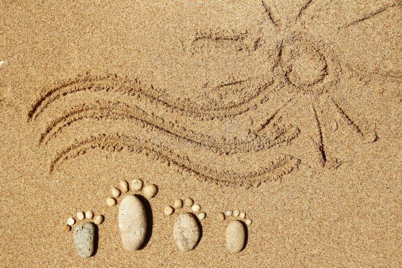 石头家庭的脚在海的 免版税库存图片