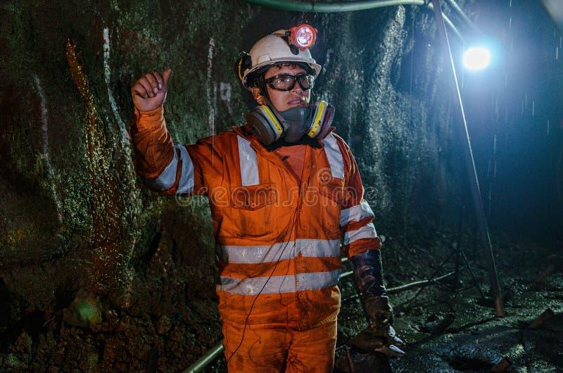 矿工和大机器在矿里面 免版税库存图片