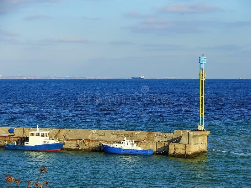 码头在蓝色海,在附近小船 免版税库存图片
