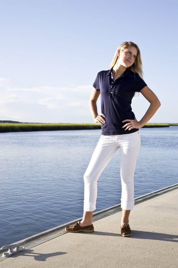 码头女孩被摆在的常设少年水 免版税库存图片