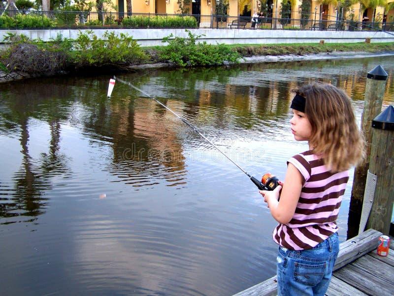 码头捕鱼女孩少许  库存图片