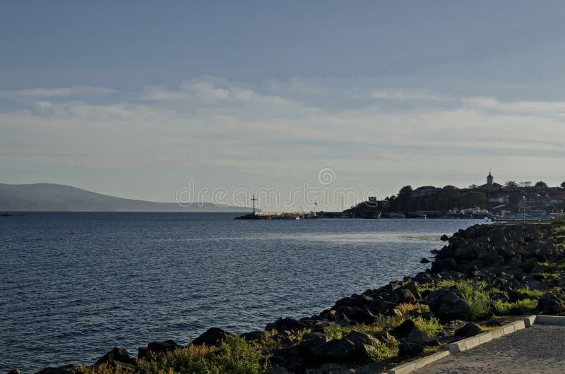 码头海景有十字架的在渔船的末端在与海角Emine的黑海和巴尔干山在古老Nessebar附近 免版税库存照片