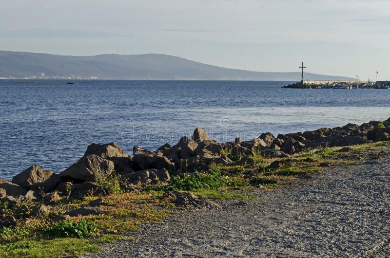 码头海景有十字架的在渔船的末端在与海角Emine的黑海和巴尔干山在古老Nessebar附近 免版税库存图片