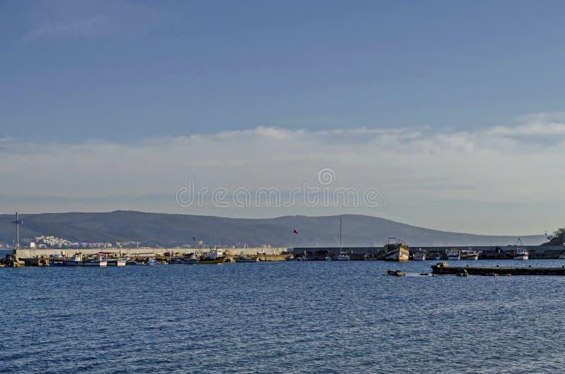 码头海景有十字架的在渔船的末端在与海角Emine的黑海和巴尔干山在古老Nessebar附近 库存图片