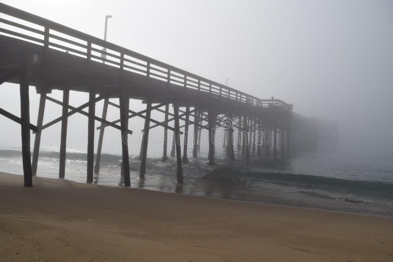 码头消失入与波浪的雾 免版税库存图片
