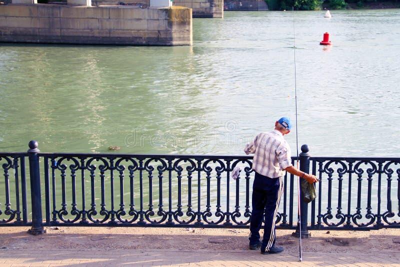 码头的渔夫有一根钓鱼竿的 有栏杆的码头由河 在码头的金属栏杆 渔夫在桥梁下 免版税库存照片