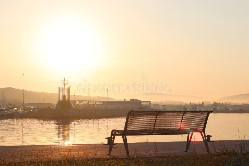 码头的空的时髦的商店在入口的水附近对早晨黎明的光芒的小游艇船坞 库存图片
