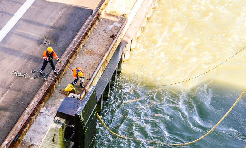 码头工人在港口的船船 免版税库存照片