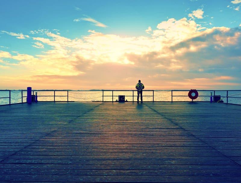 码头的单独在扶手栏杆的人和神色到水里 晴朗的天空,光滑的水平面 库存照片