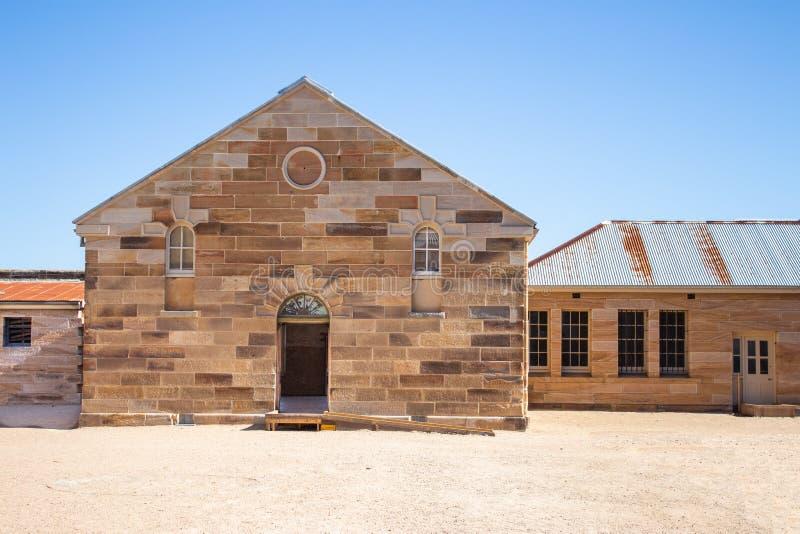 砂岩砖证明有罪修建了与装饰石制品,波状钢屋顶,被成拱形的门道入口,pebbled庭院的大厦反对 免版税库存图片