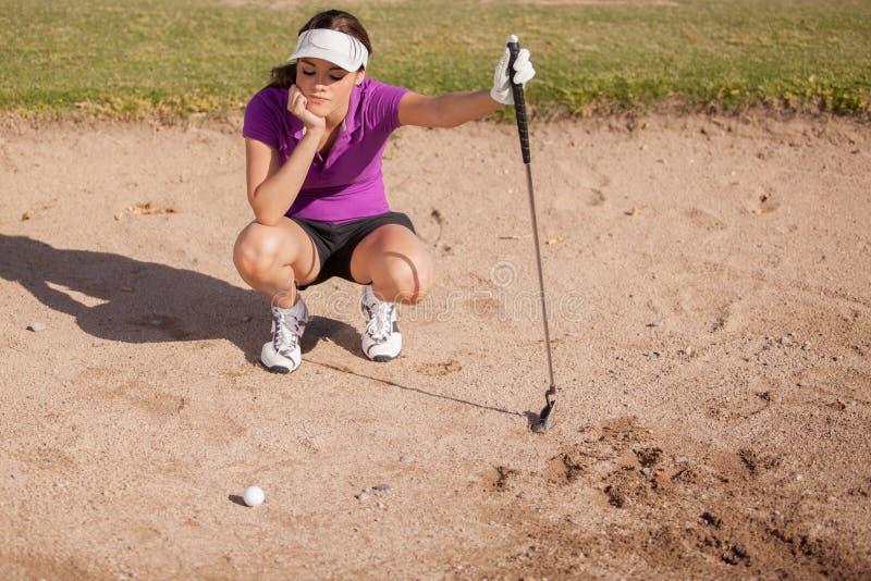 砂槽的沮丧的高尔夫球运动员 库存照片