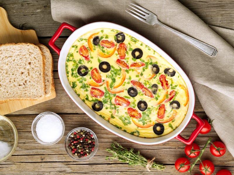 砂锅盘,可口热的煎蛋卷用蕃茄,橄榄,辣椒的果实 老木纹理背景,顶视图 库存照片