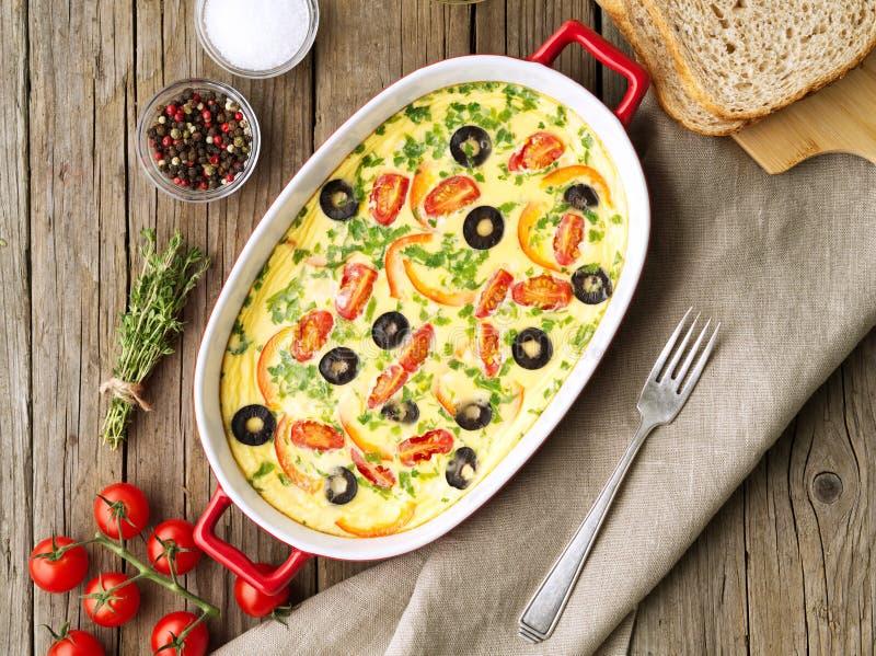 砂锅盘,可口热的煎蛋卷用蕃茄,橄榄,辣椒的果实 老木纹理背景,顶视图 免版税图库摄影