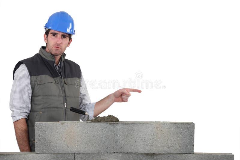 砌砖工指向 库存图片