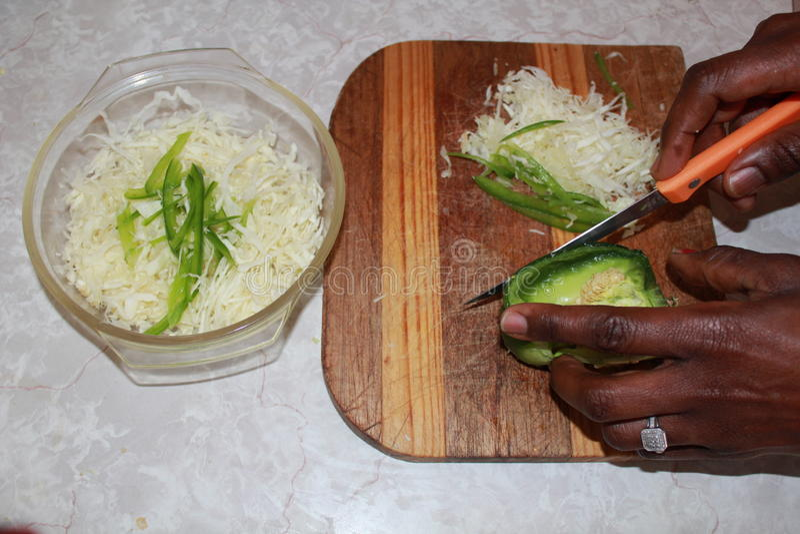 砍圆白菜和青椒的手 库存照片