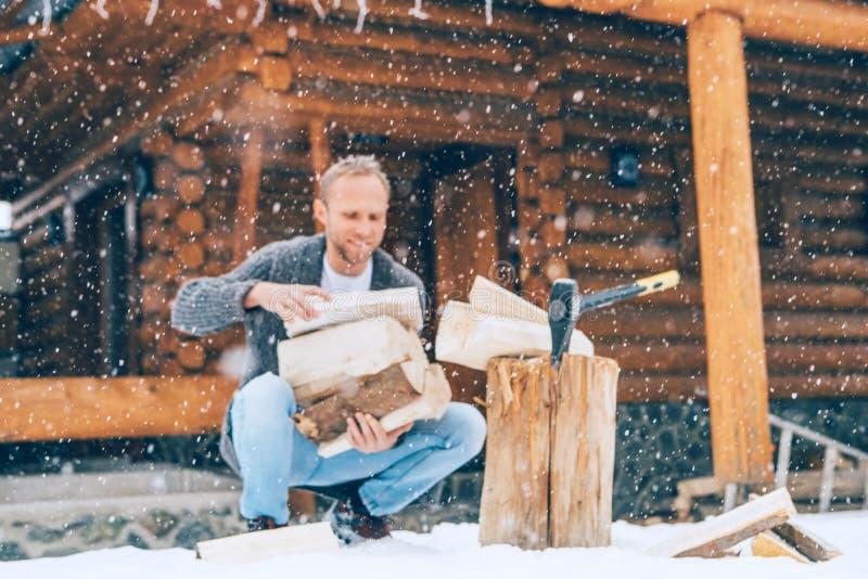 砍在多雪的围场的人木头一个房子壁炉的有重的雪花背景 冬天乡下假日概念图象 库存照片