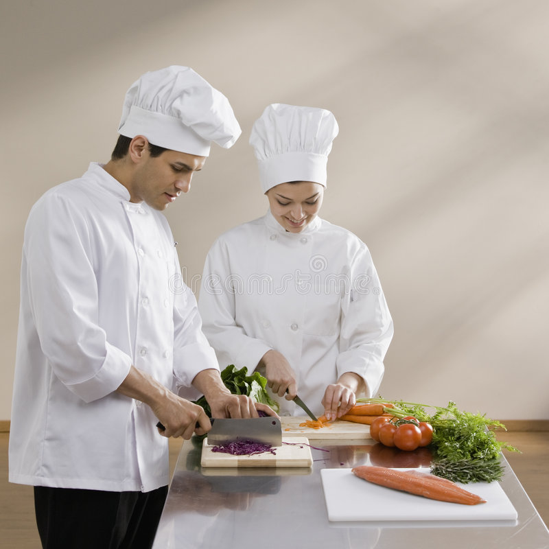 砍女性男性蔬菜的主厨 免版税库存照片