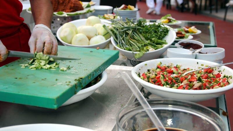 砍沙拉成份的厨师 免版税库存图片