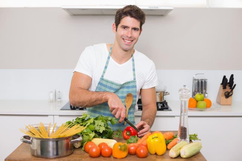 砍菜的微笑的年轻人在厨房里 库存照片