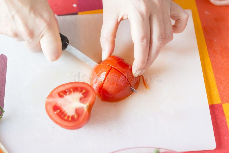 砍蕃茄的妇女的手 免版税库存照片
