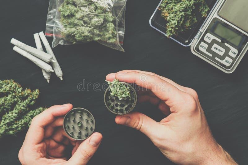 研在一个人的手上的大麻的研磨机反对席子葡萄酒颜色 免版税图库摄影