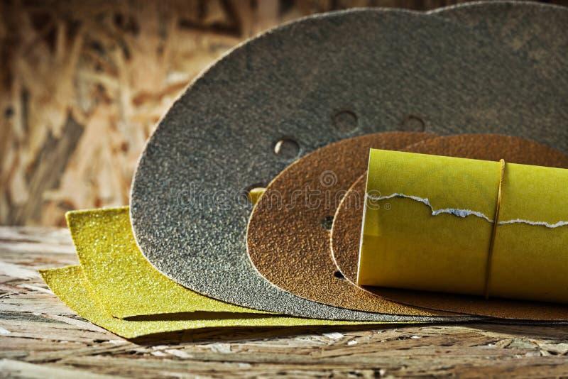 研磨剂环绕沙纸方形和滚动的板料在plywoo的 免版税库存图片