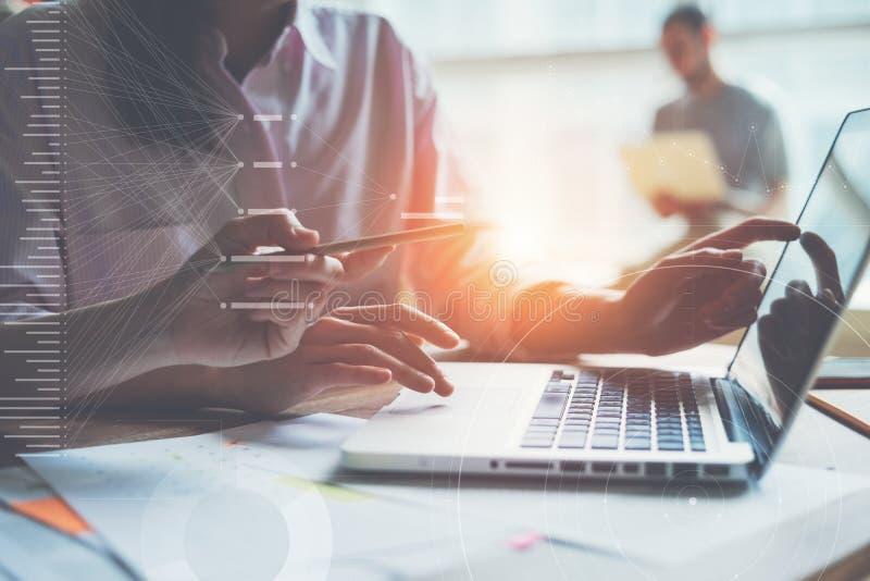 研究一个项目的创造性的队在顶楼办公室 谈论两名的妇女销售计划 膝上型计算机和文书工作在桌上 免版税库存图片