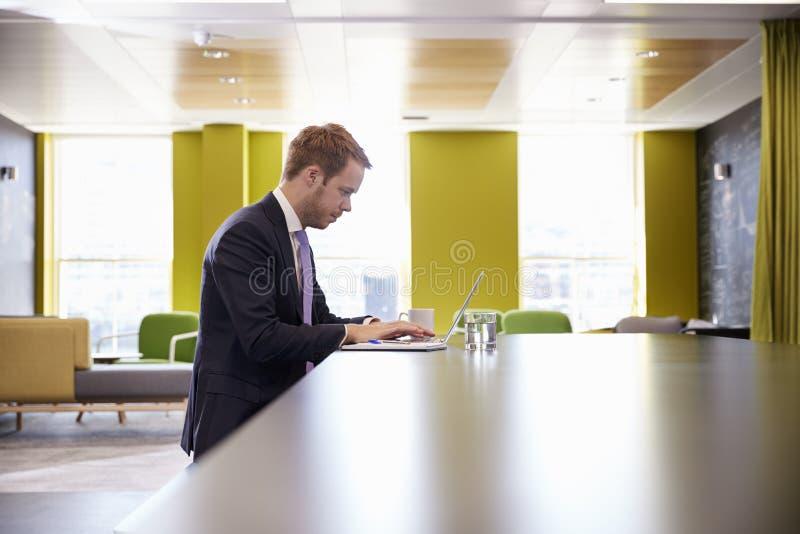 研究一台膝上型计算机的年轻商人在遇见区域的办公室 免版税库存照片