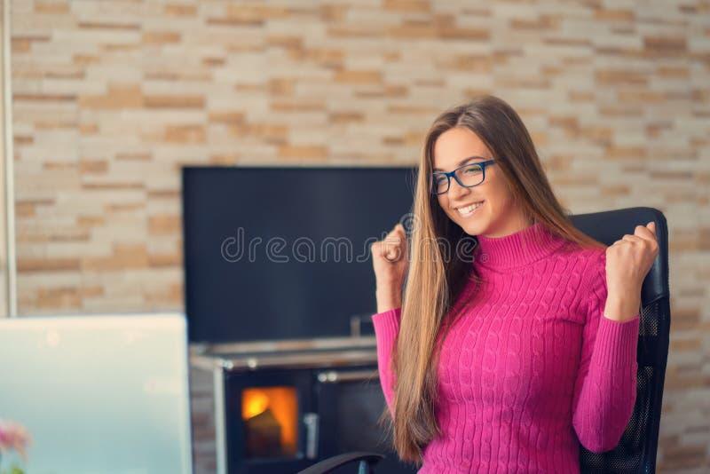 研究一台膝上型计算机的愉快的年轻女人在她的家庭办公室 成功的概念 免版税库存图片
