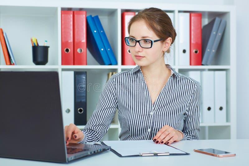 研究一台膝上型计算机的美丽的年轻女实业家在办公室 免版税库存图片