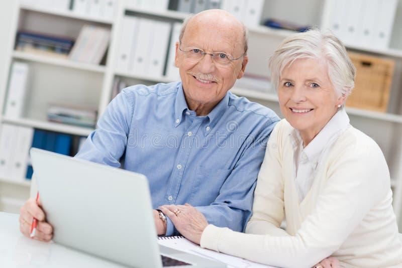 研究一台膝上型计算机的资深夫妇在办公室 库存图片