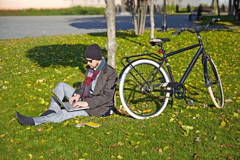 研究一台膝上型计算机的年轻人在秋天公园。 库存图片