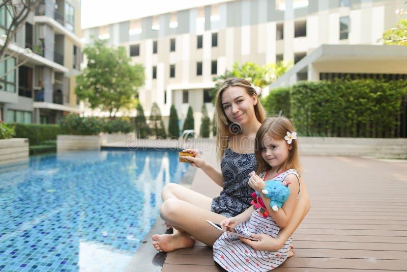 研究与膝上型计算机的假期的年轻母亲在游泳池附近 库存照片