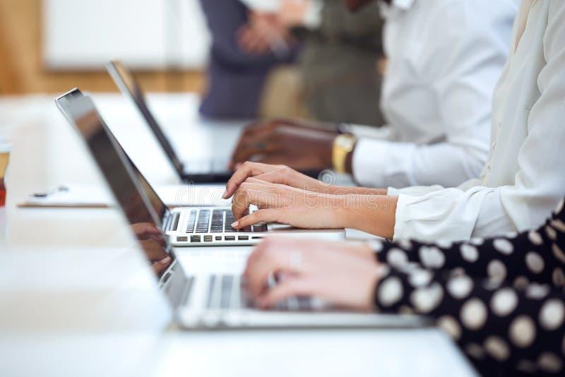 研究他们的在coworking的地方的膝上型计算机的年轻买卖人手 免版税库存照片