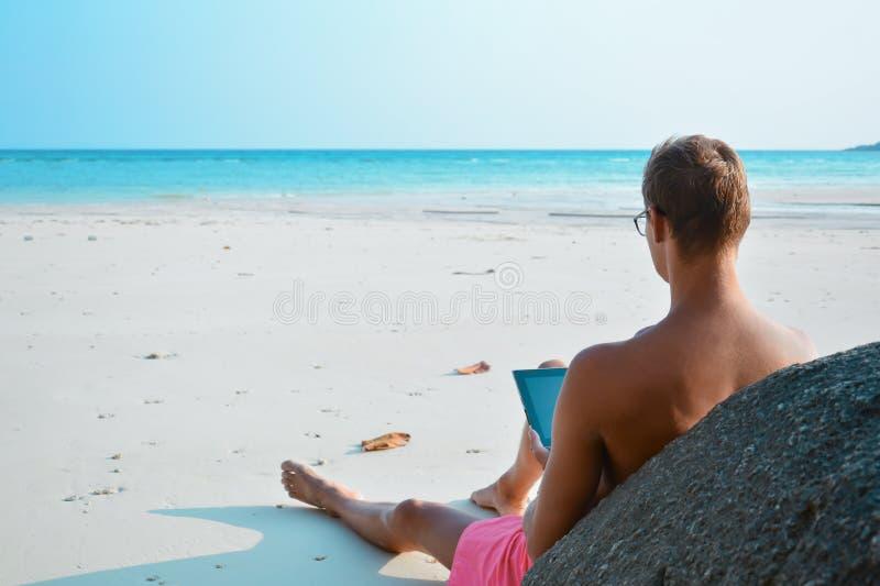 研究他的在海滩的膝上型计算机的年轻人 从年轻人后面的看法有笔记本的在的海岸自由职业者 库存照片