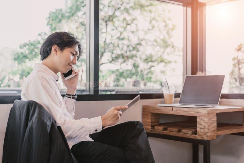 研究他的膝上型计算机的年轻人的播种的图象在咖啡馆,商人手背面图繁忙使用膝上型计算机在办公室 库存照片