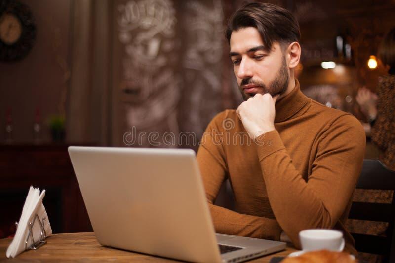 研究他的膝上型计算机的有胡子的商人在葡萄酒咖啡馆 免版税库存图片