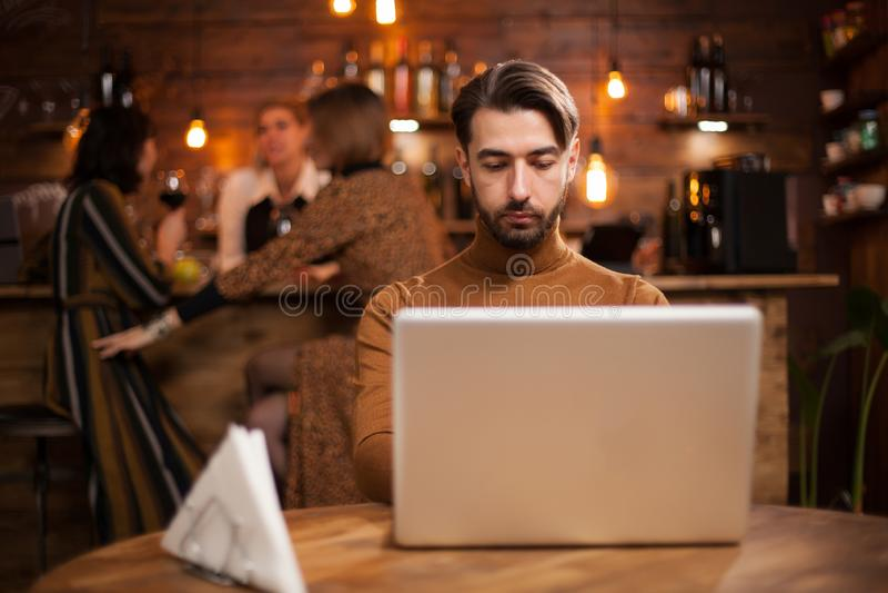 研究他的膝上型计算机的英俊的商人在葡萄酒咖啡馆 免版税库存图片