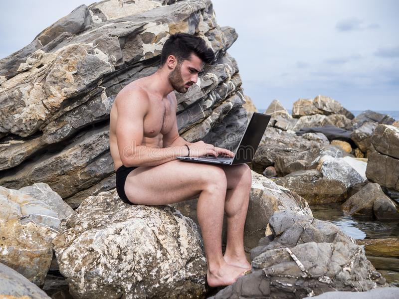 研究便携式计算机的年轻人在海滩 免版税库存照片