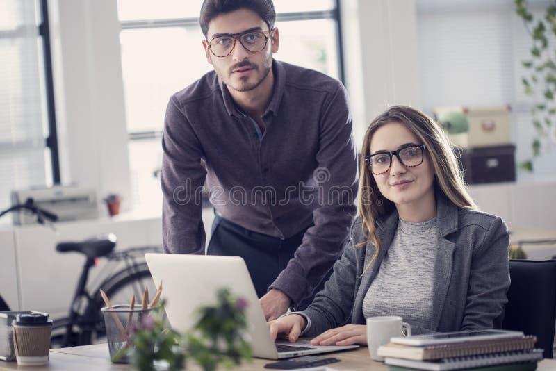 研究便携式计算机的年轻同事 免版税库存照片