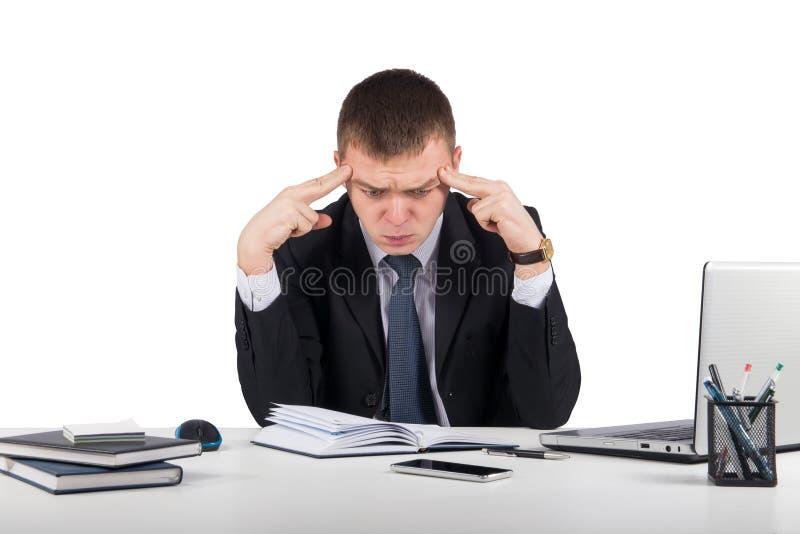 研究便携式计算机的沮丧的年轻商人在办公室 免版税库存照片