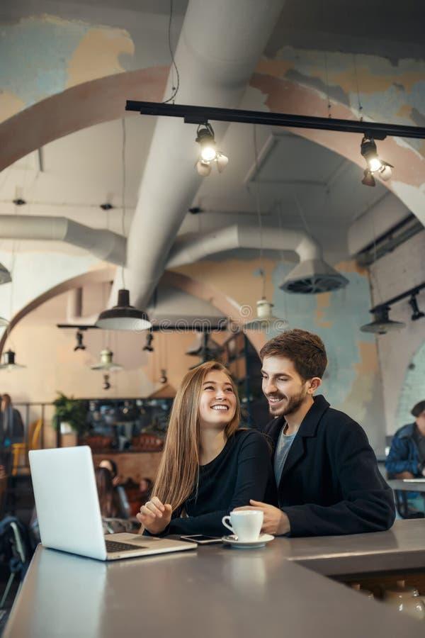 研究便携式计算机的美好的愉快的夫妇在咖啡馆酒吧的咖啡休息期间 库存照片