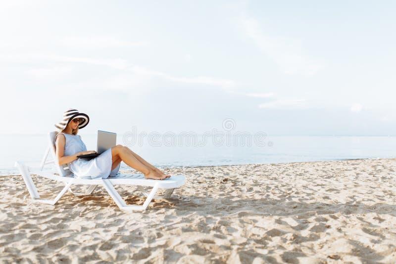 研究假期的自由职业者女孩,在美丽的海前面,与膝上型计算机坐海洋 免版税库存照片