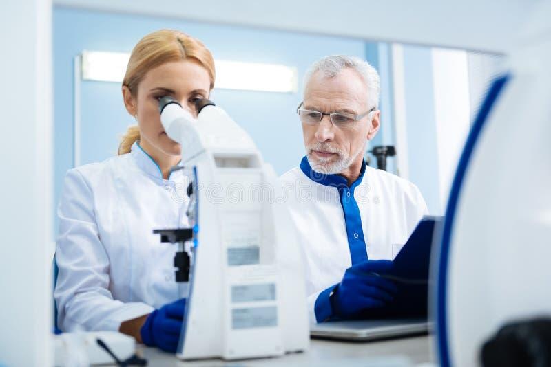 研究员与显微镜和片剂一起使用 免版税库存图片