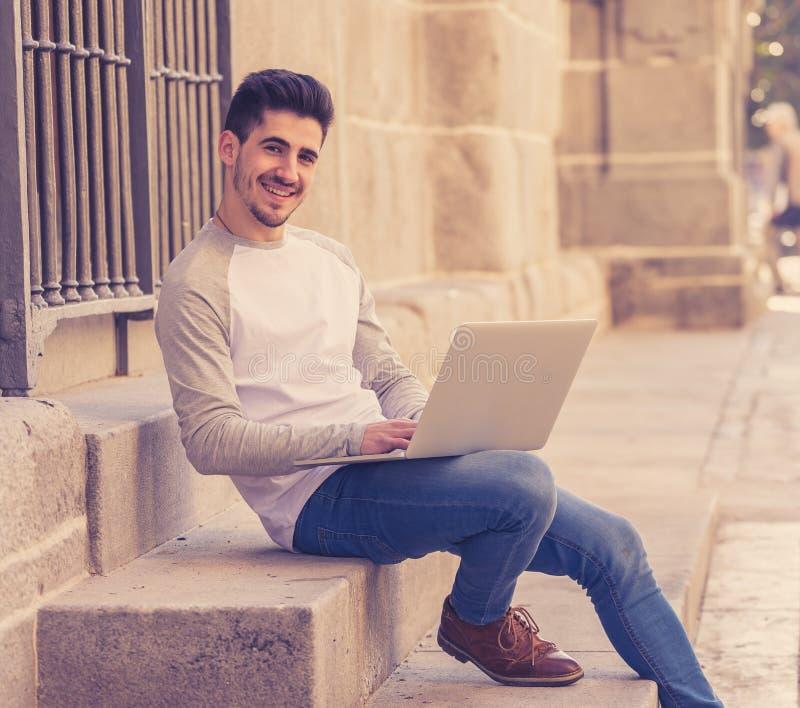 研究和学习在欧洲人的膝上型计算机的年轻帅哥 免版税库存照片