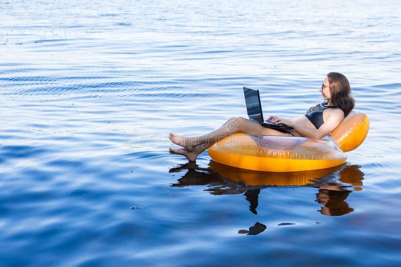 研究在一个可膨胀的圆环在海,研究的概念的一台膝上型计算机的女商人假期 免版税图库摄影