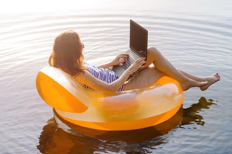 研究在一个可膨胀的圆环的一台膝上型计算机的女商人在 图库摄影