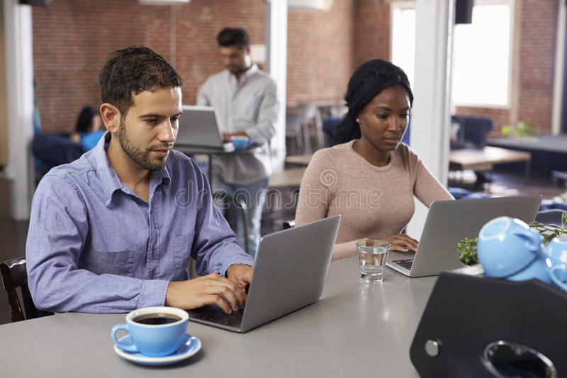 研究在办公室咖啡馆的膝上型计算机的买卖人 免版税库存图片